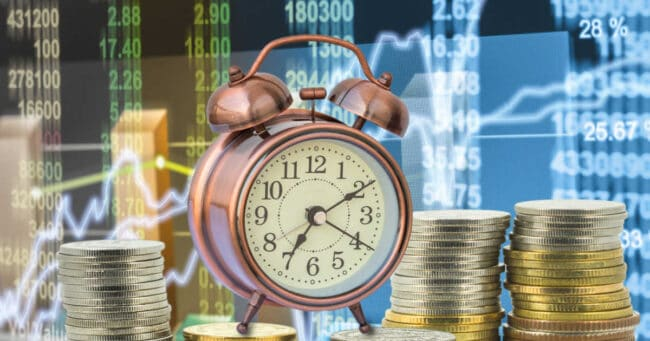 investing concept money clock and stock market ticker