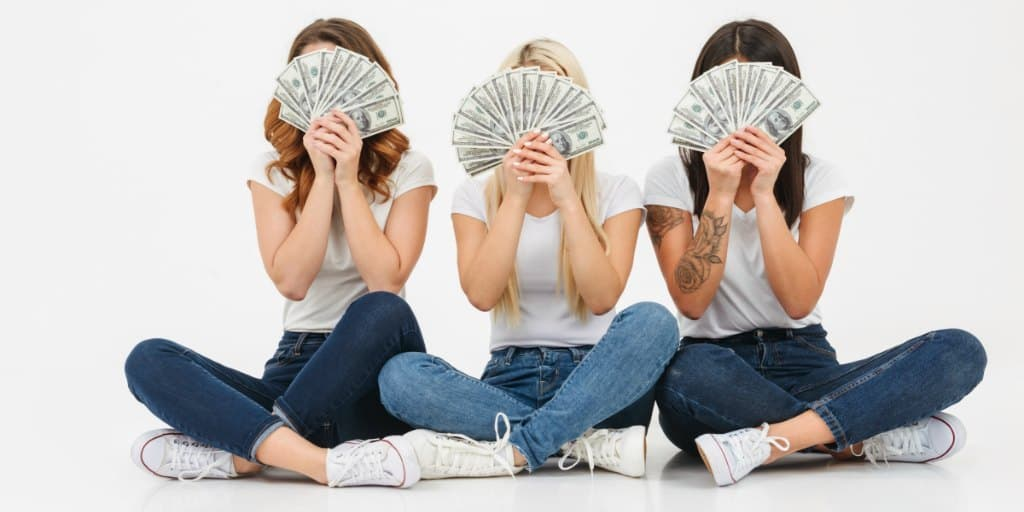 3 female teens fanning cash money in front of their faces