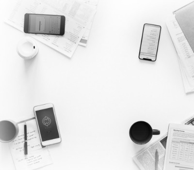 white desktop with three cell phones and various papers strewn across it