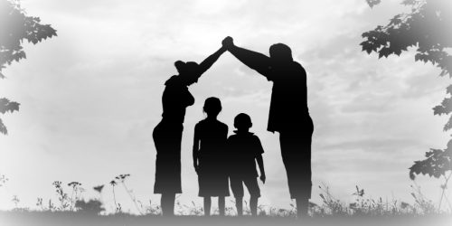 silhouette of a young family of four with parents holding hands above the heads of two children symbolizing an act of protection