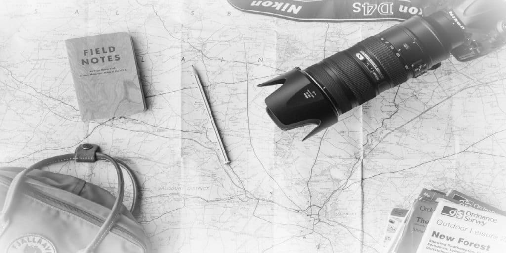 black and white photo of a map, camera, brochures, and other travel related items