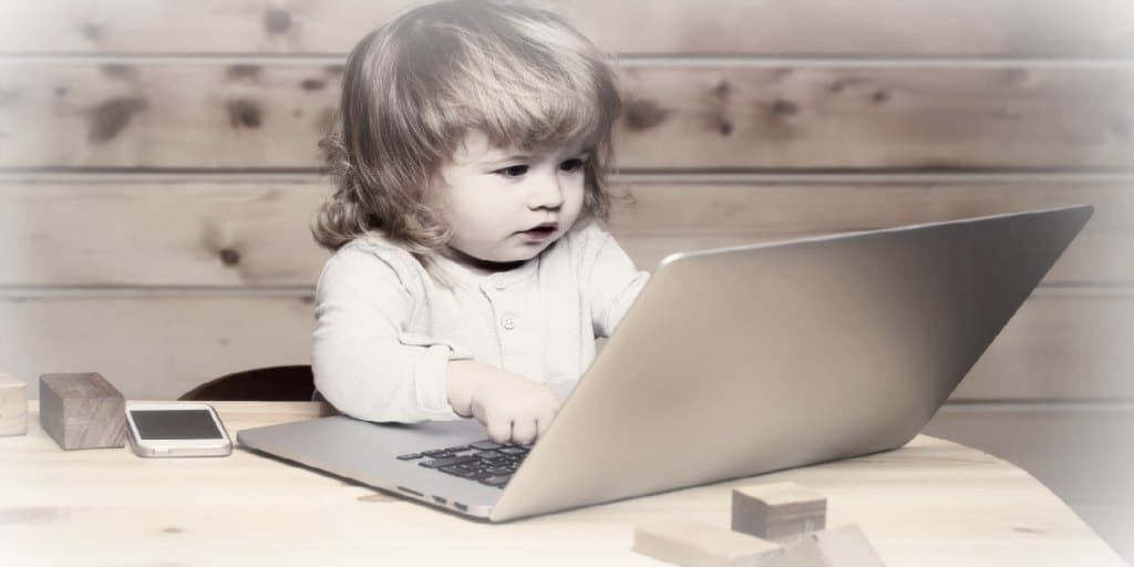 building credit score - young child with her fingers on the keyboard of a laptop computer