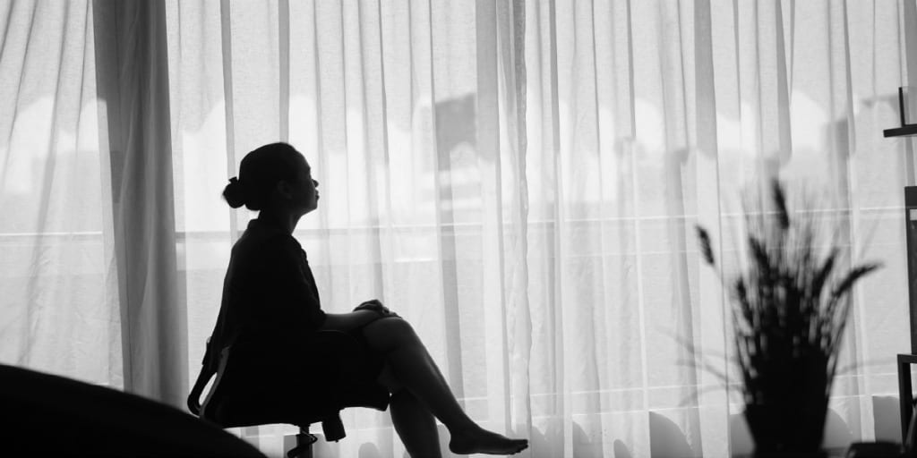 silhouette of women sitting in office chair looking out big window