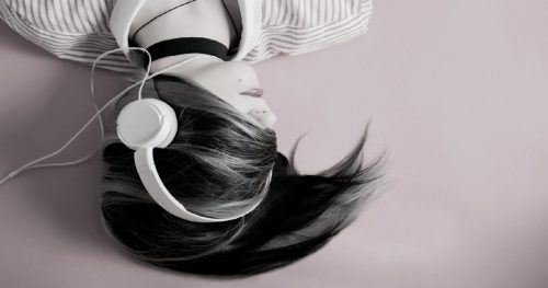 dark haired woman with her hair wrapped around her head and headphones on