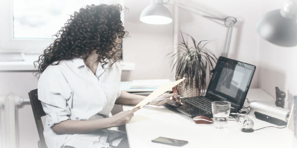 women working at a home office desk with a laptop and desk lamp on