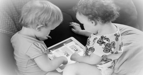 black and white image of two young babies looking at an iPad