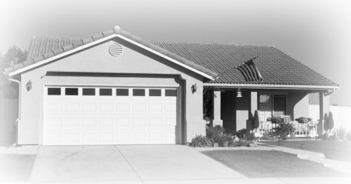 black and white image of a single family ranch home with 2-car garage