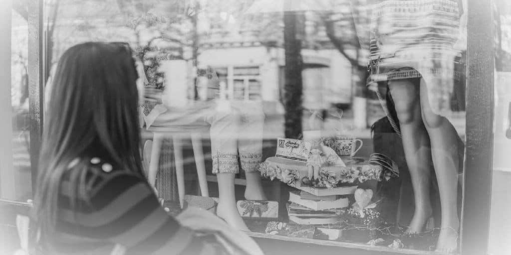 dark haired woman looking in a storefront window