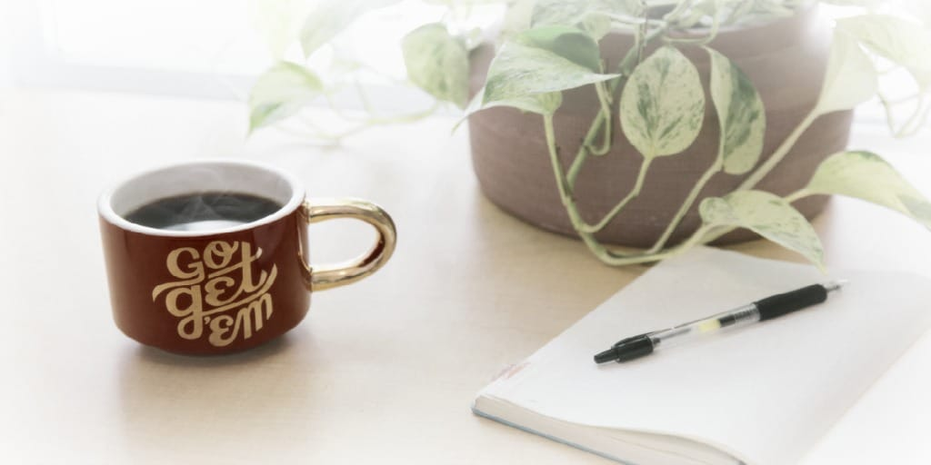 open blank notebook with pen, mug filled with coffee, and a green plant on a desk