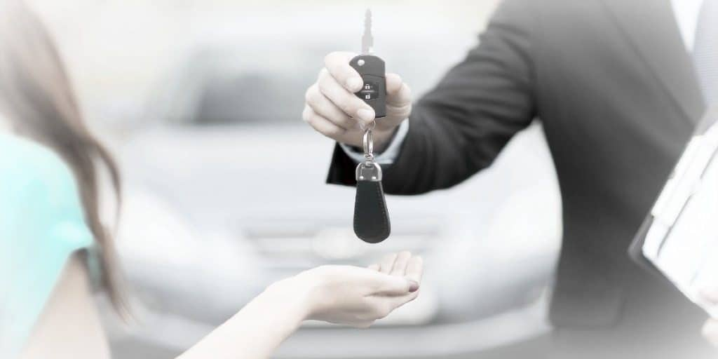 man giving a car key to a female