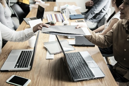 two people tugging on opposites of a work folder, sitting around a work table