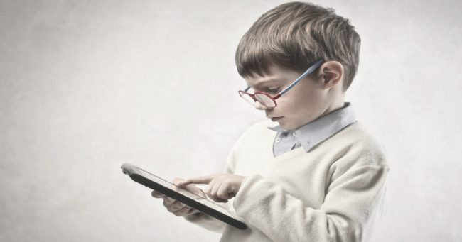 male child wearing glasses looking at a tablet