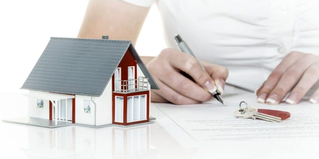 a woman signs a financing contract for buying a home