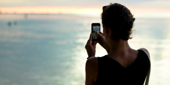 women holding a cell phone looking over water