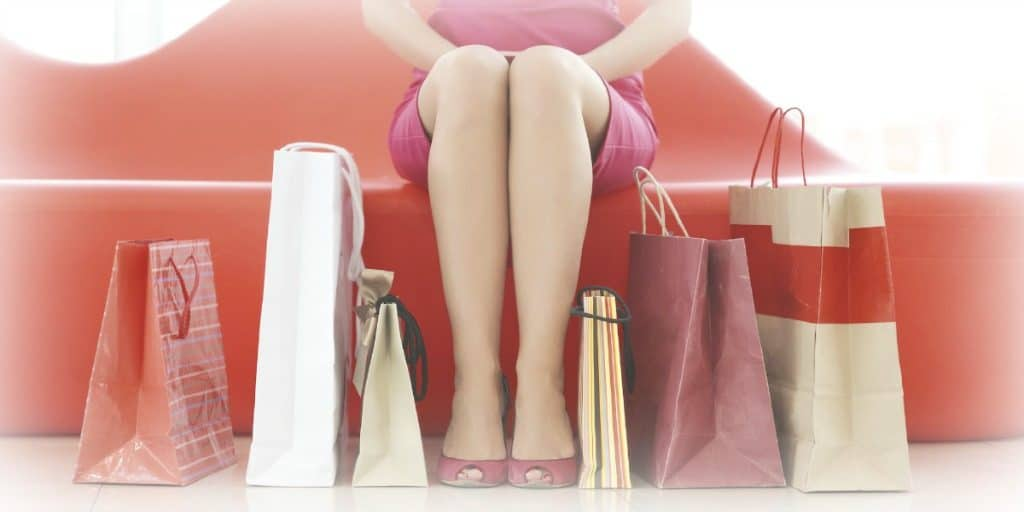 holiday shopping bags sitting on the floor at a women's feet
