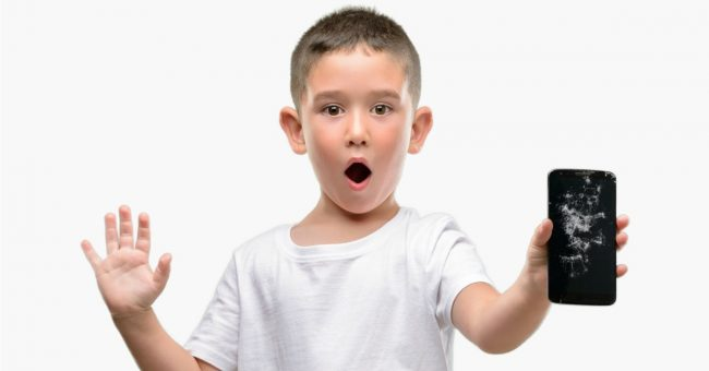 Dark haired little child holding broken smartphone scared in shock with a surprise face, afraid and excited with fear expression