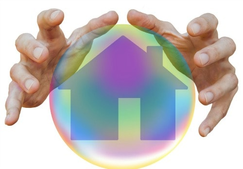 two hands around an illustration of a crystal ball with a house appearing in it