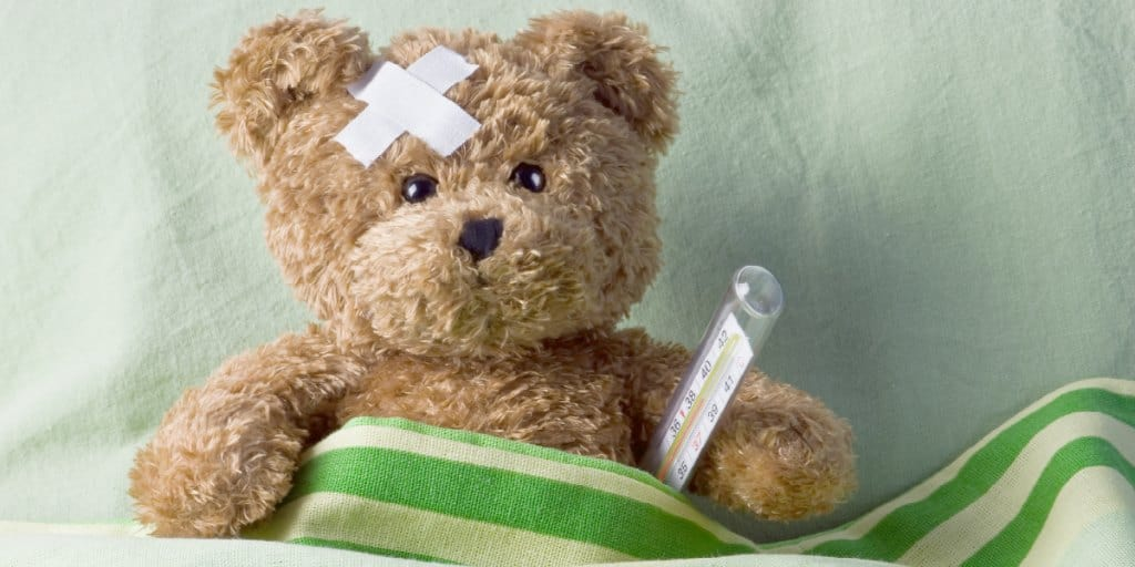 sick teddy bear in bed with a thermometer under his arm