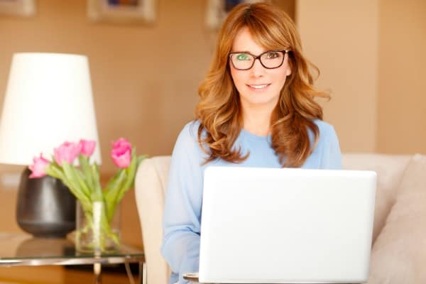 women wearing glasses and working on a laptop