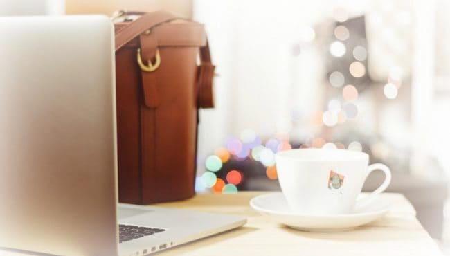 laptop, leather briefcase, and cup of tea on a desk