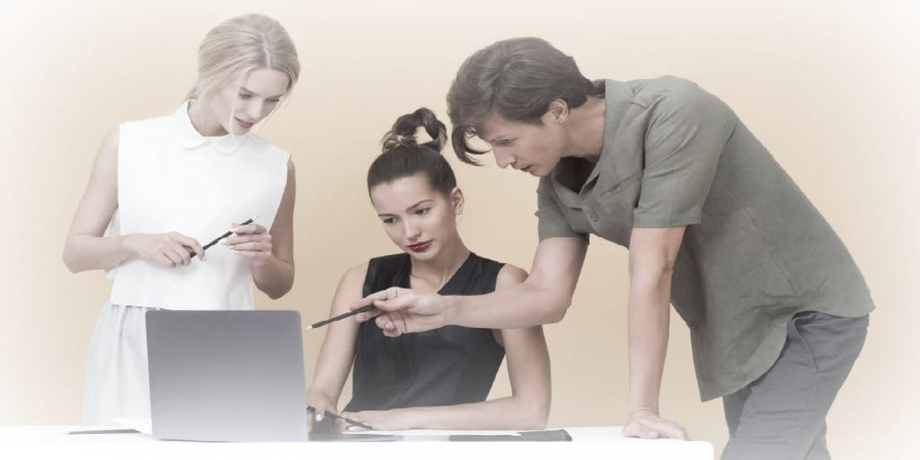 man and two woman coworkers looking at the screen of a laptop
