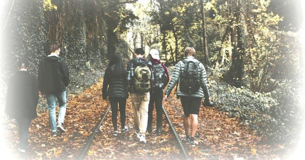 teenagers walking down railroad tracks wearing school backpacks
