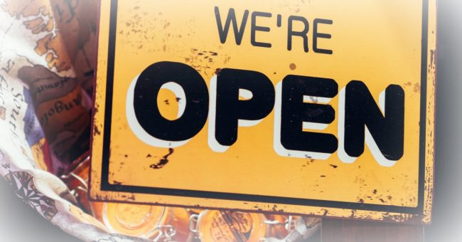 yellow and black open for business sign