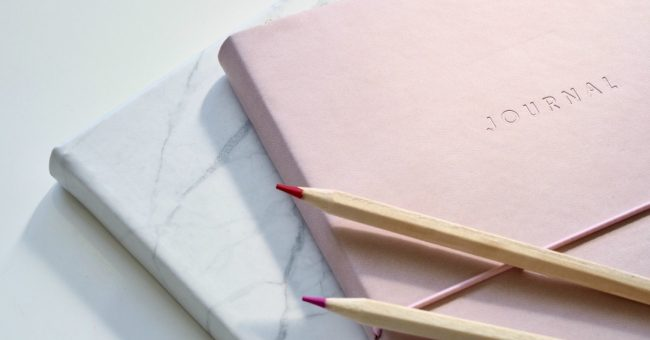 pink journal, white journal, two pink colored pencils