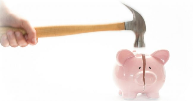 hammer hovering over a piggy bank - smashing your 401k bank for a loan