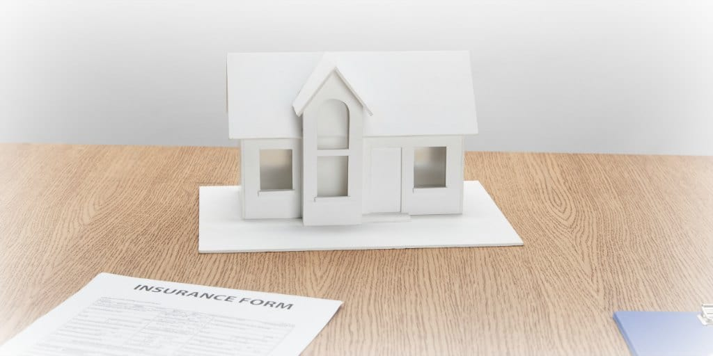 white model of a home and an insurance form on a brown desk