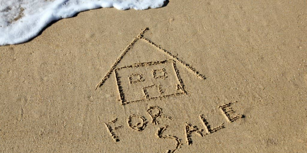 house for sale written in sand at the beach