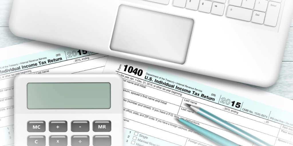 tax forms, calculator, and laptop ready to prepare taxes