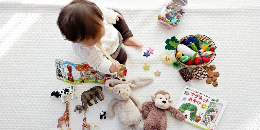 baby surrounded by baby toys