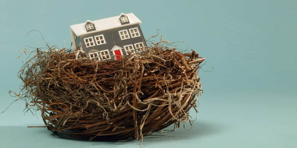small model of a house sitting in a nest-a reverse mortgage will allow you to tap the nest egg