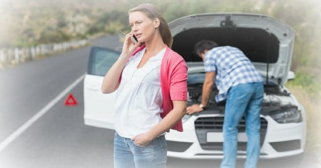 Couple calling AAA roadside service after a car breakdown at the side of the road