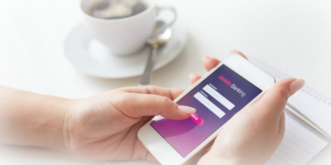 female holding a phone with the Ally Bank app showing