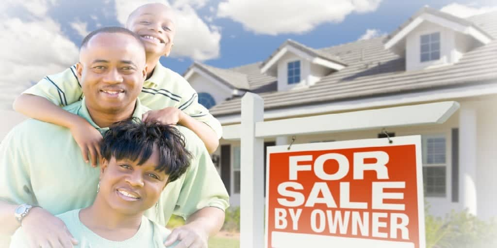 young family in front of a for sale by owner home