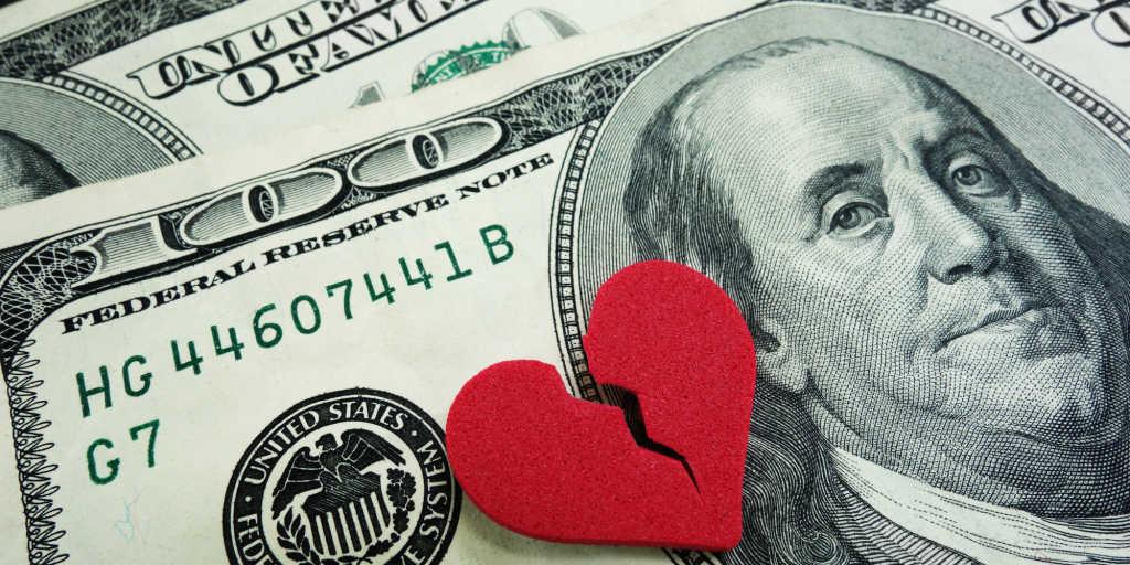 closeup of a broken red heart on cash - divorce concept