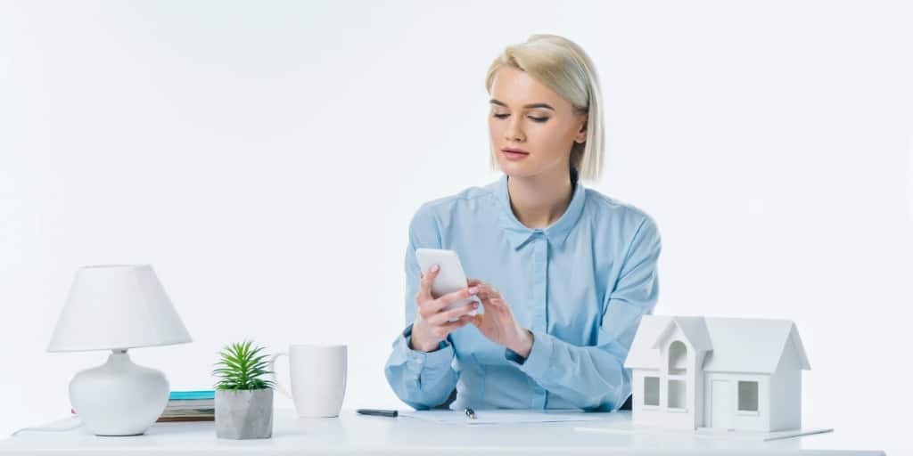 young female real estate agent looking at her smartphone