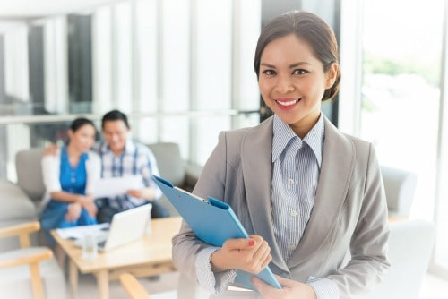 cheerful female real estate agent with a clipboard