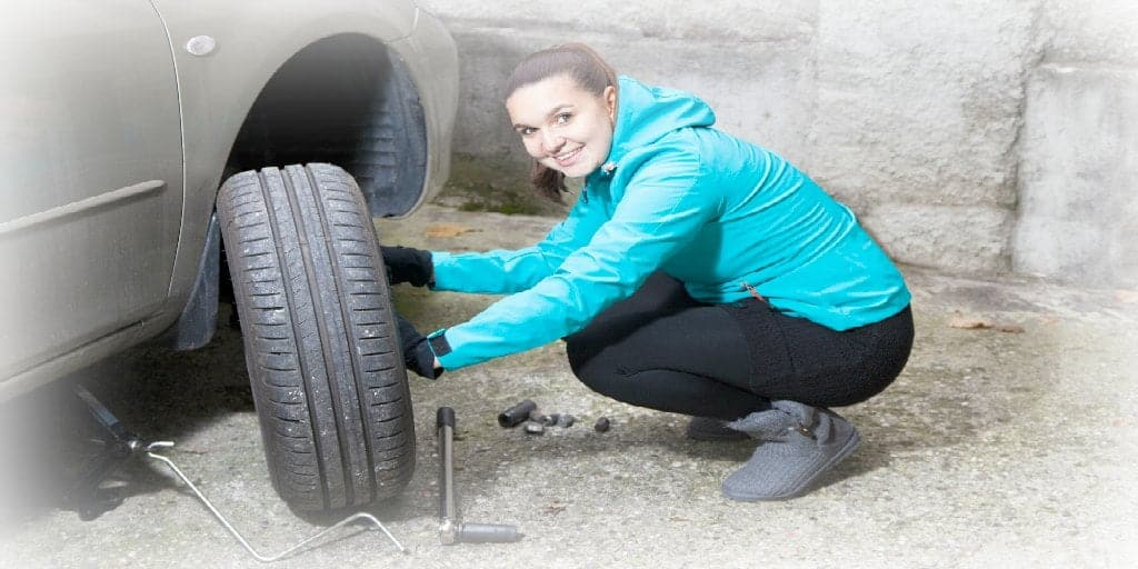 female changing a tire on a car