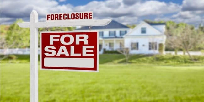 red foreclosure for sale sign in front of a white home