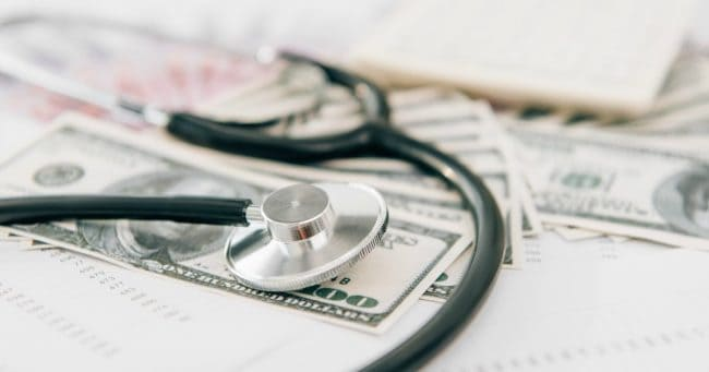 stethoscope on top of cash representing healthcare costs