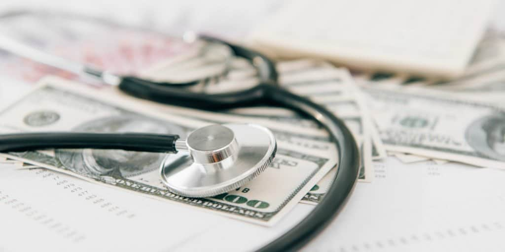 stethoscope on top of cash representing healthcare costs in retirement