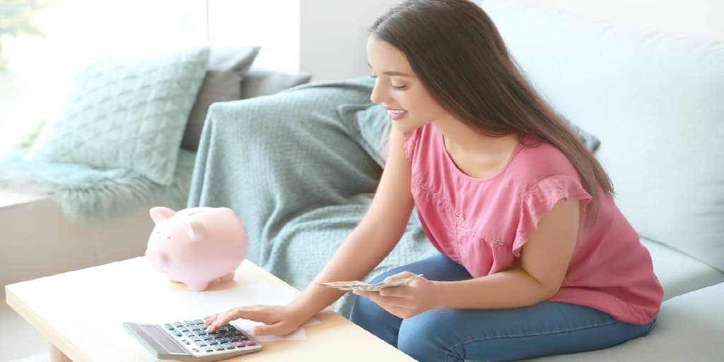 young female using calculator to determine investing strategy, lump sum or dollar cost averaging