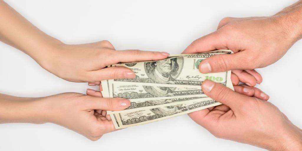 a couple grabbing opposite ends of 100 dollar bills