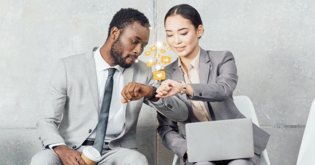 couple comparing smart technology they are wearing on their wrists