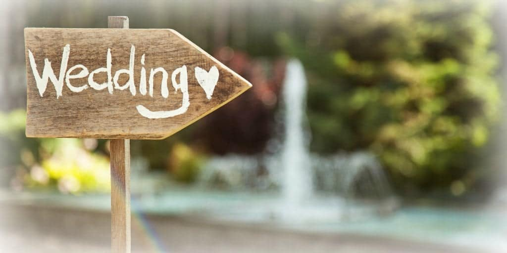 wooden arrow with the word wedding pointing the direction for guests attending a wedding
