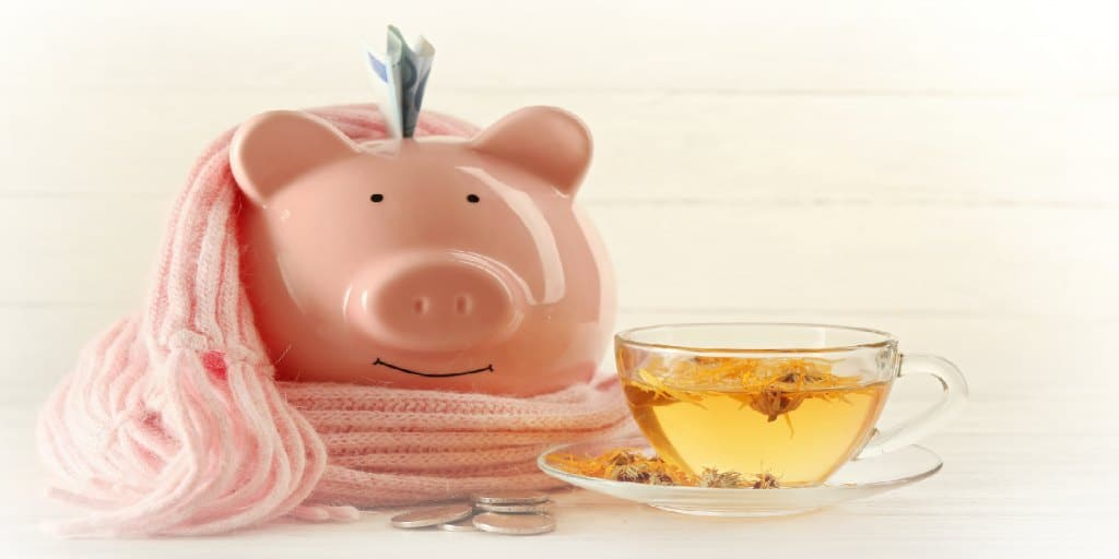 Piggy bank with scarf and herbal tea. Financial health concept