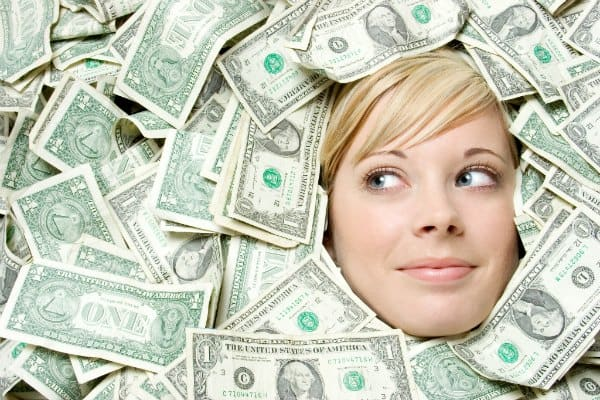 female face peaking out from under a pile of dollar bills